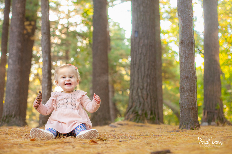 A Beautiful baby in a pink sweater enjoying a warm autumn sunrise at a wooded arboretum.
