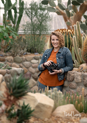 Becky aka Petal Lens Photography leaning against a stone wall holding her camera smiling right at YOU in front of cactuses in an indoor desert environment.